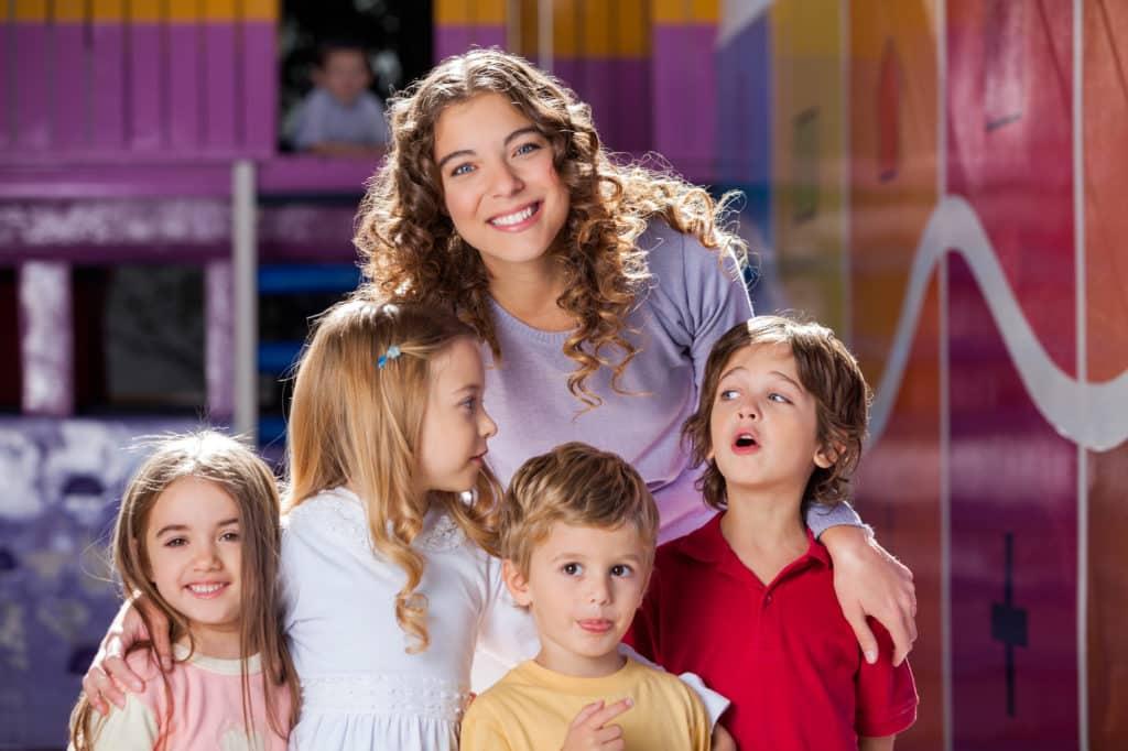 Happy Teacher With Cute Children In Preschool