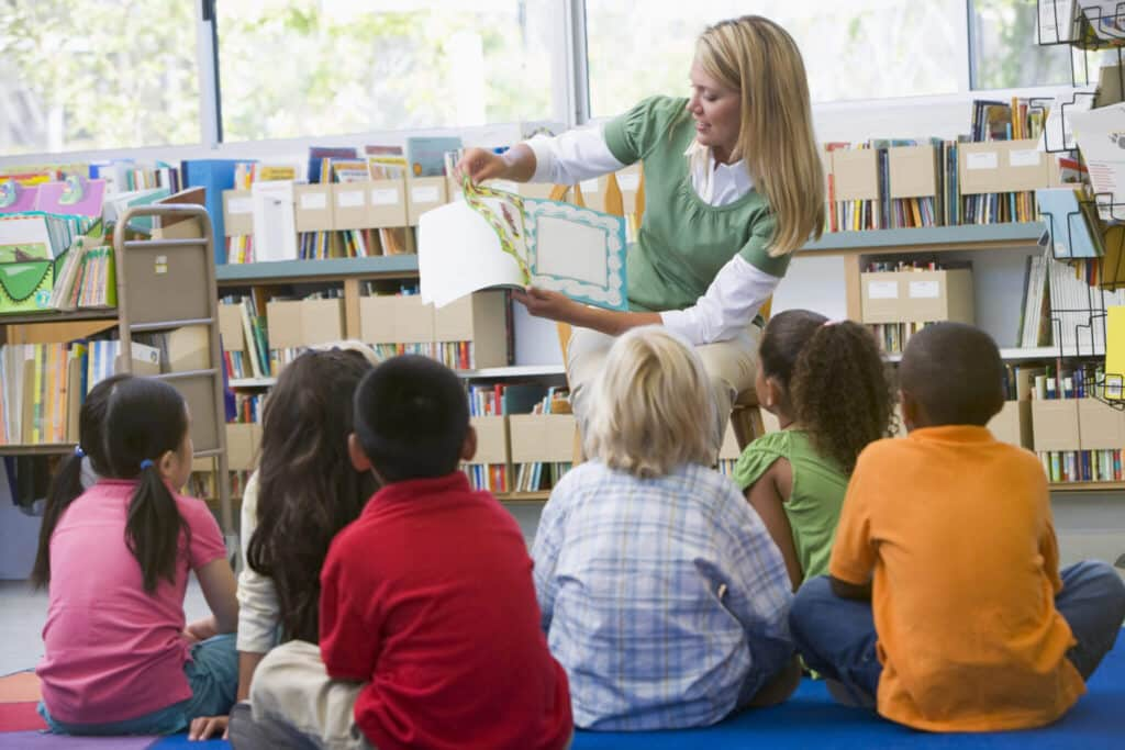 Kindergarten teacher reading to children in library