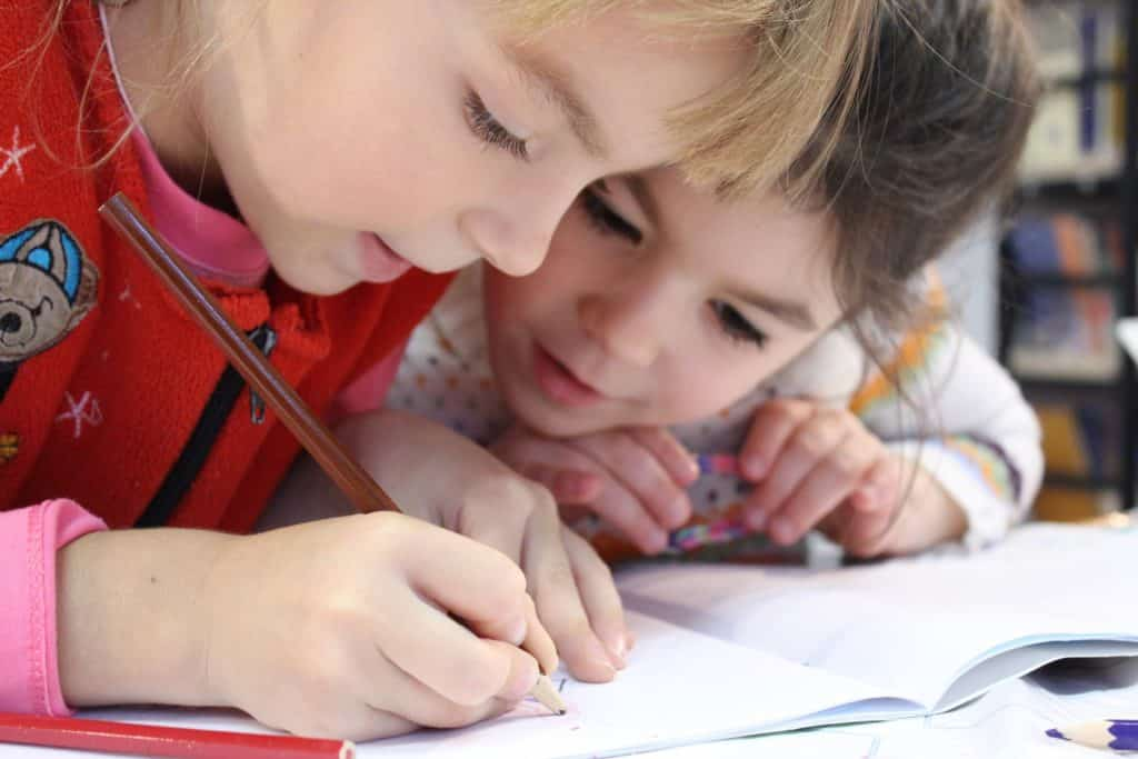 Two girls use colored pencils at a child care center.