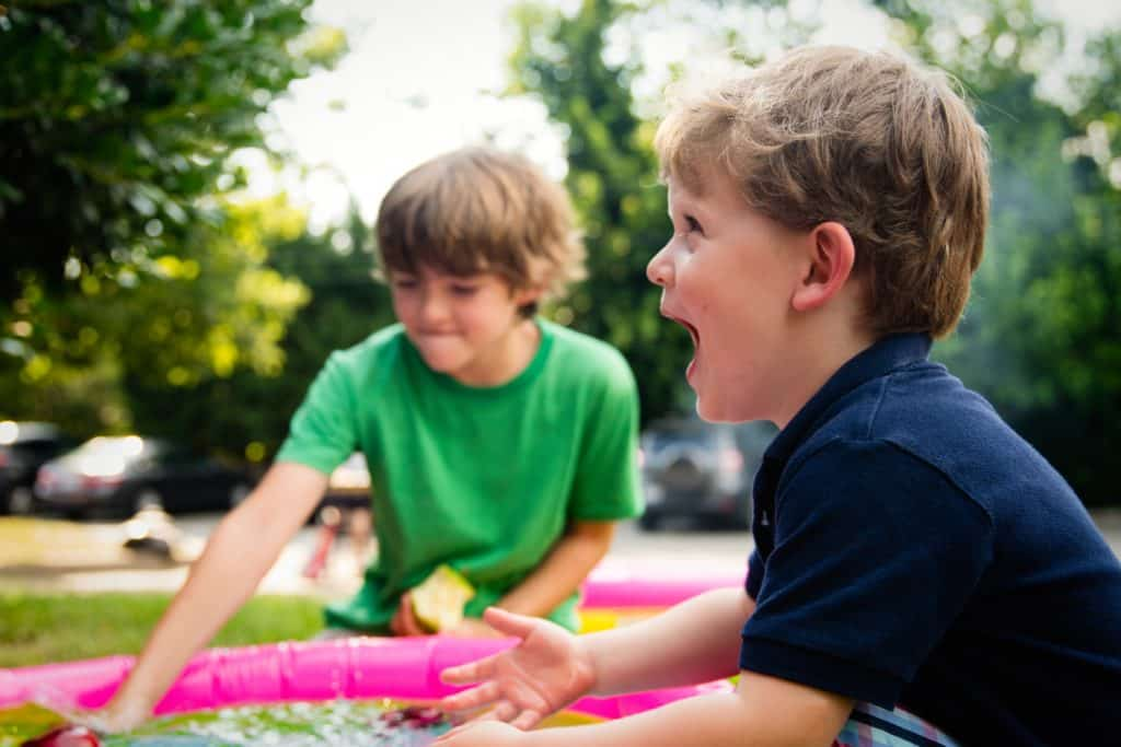 Two boys play outside at a child care center.