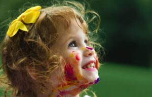 Little girl at a child care center with paint on her face.