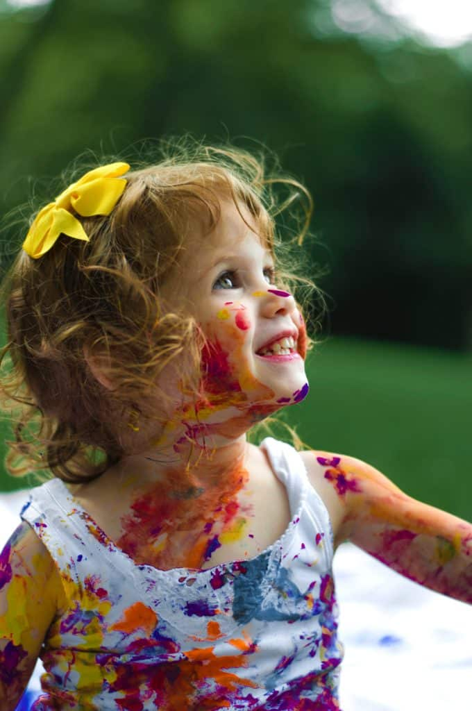 Little girl with a yellow bow in her hair and paint on her face at a child care center.