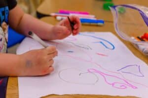 A child at a child care center draws a picture.