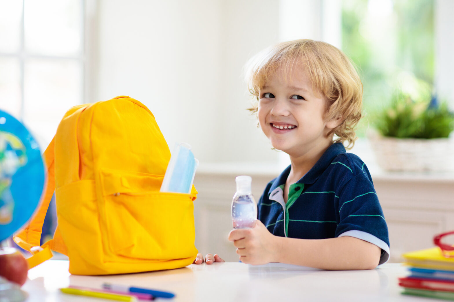 Child at a childcare center prepared for COVID-19 with hand sanitizer and a face mask.