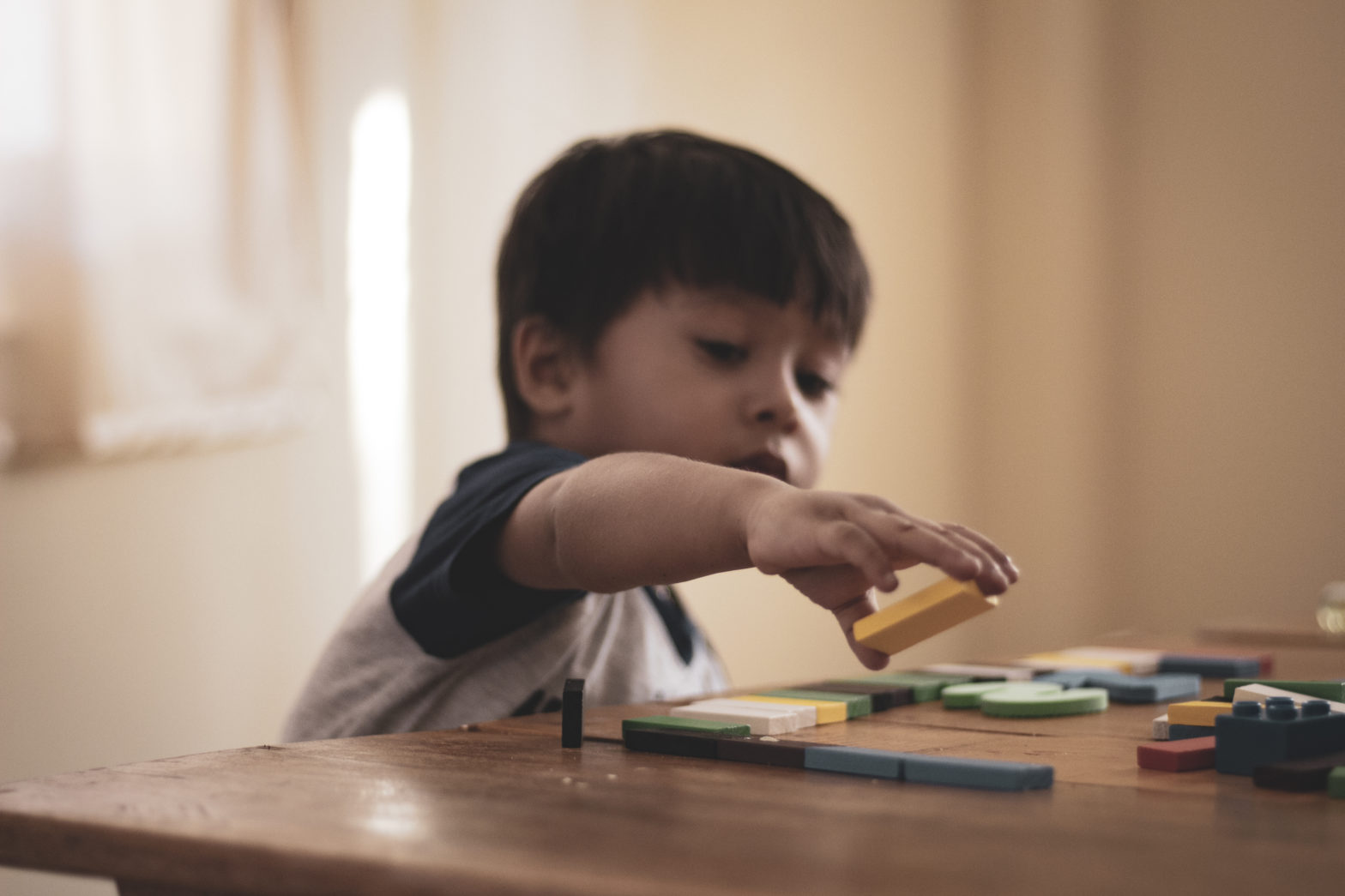 Little boy placing puzzle pieces together at a childcare center.
