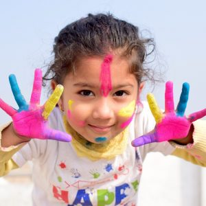 Child in a childcare center who has been finger-painting as part of a flex scheduling program