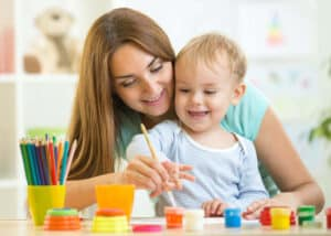 Child playing while teacher observes development milestones