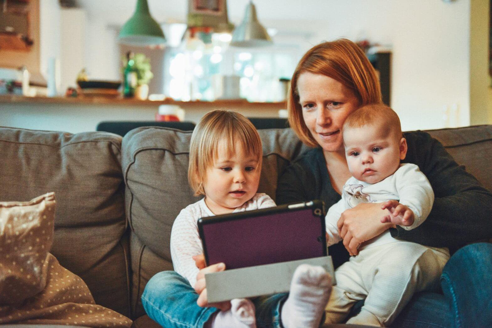 Mom on the couch with two children engaging in parent-teacher communication on a tablet.