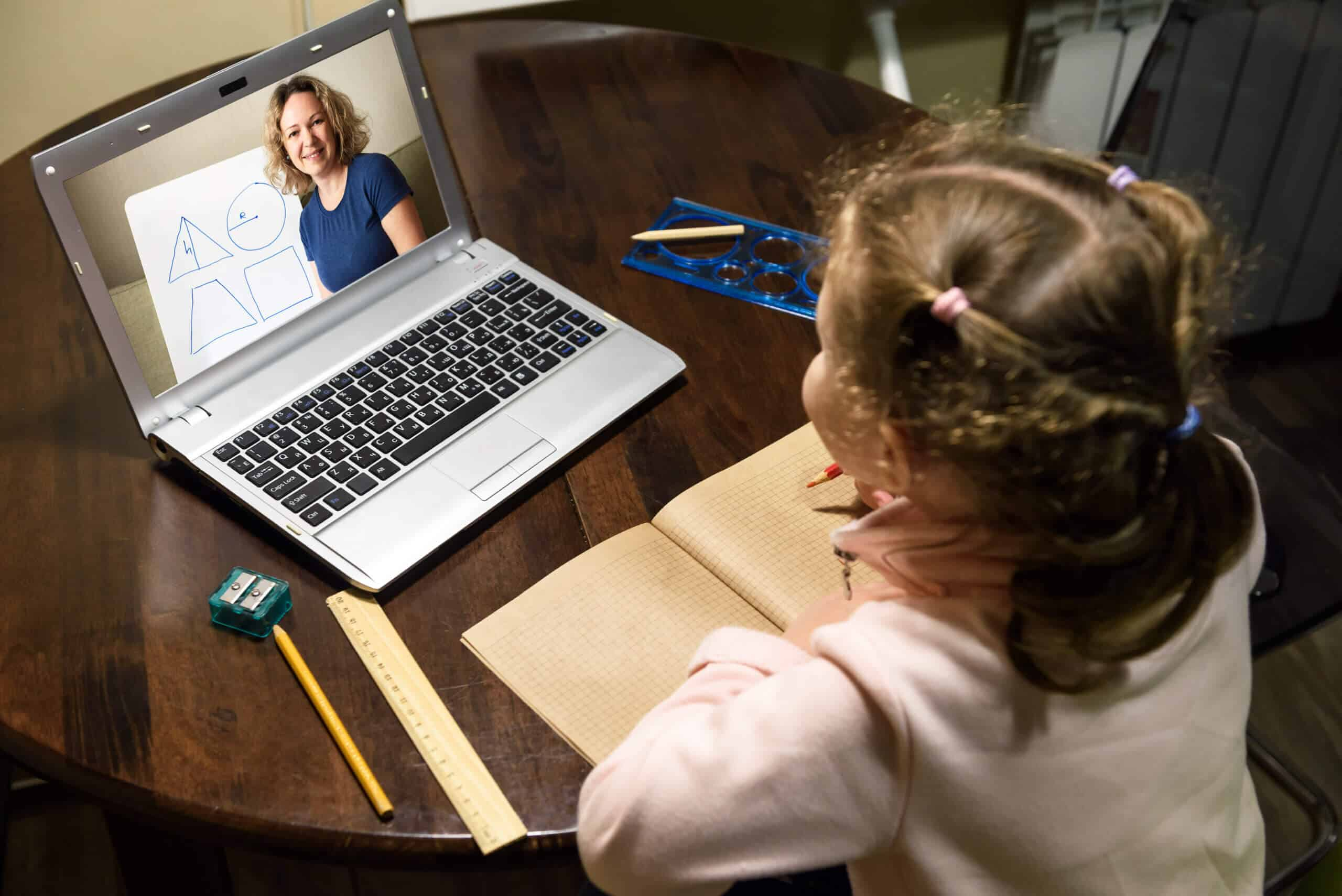 Kid virtual learning with teacher by laptop, tutor teaches preschool child during quarantine due to coronavirus.