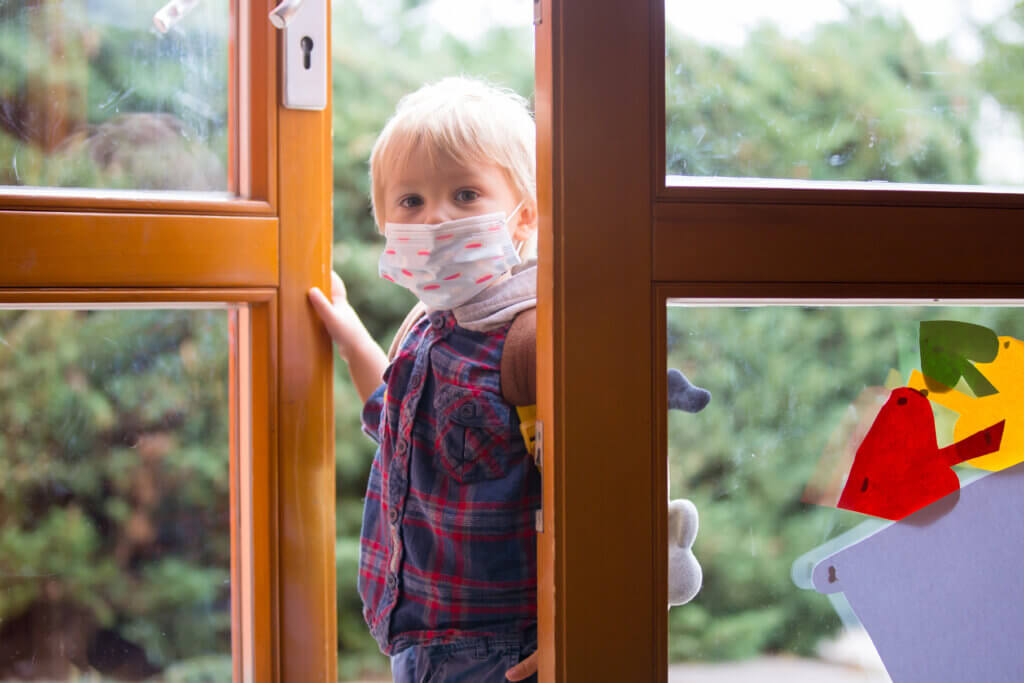 Child, putting medical protective mask before entering kindergarten