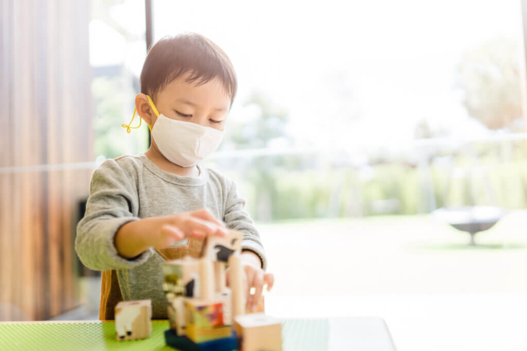 Asian toddler boy playing toy block in day care school.3.5 years old boy child wearing face mask in Day care.Covid-19 coronavirus.Nursery.Social distancing in school kid.Back to school.New normal.