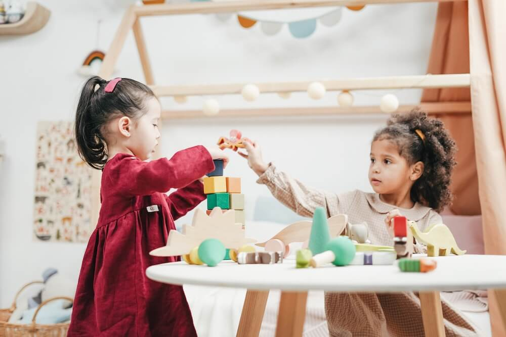 Two preschool girls playing blocks at a childcare center